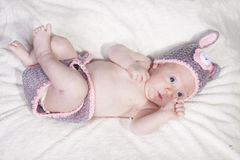 Cute baby in a bunny suit. With funny expression on furry blanket Royalty Free Stock Photography