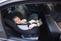 Cute baby in a car seat Stock Photos