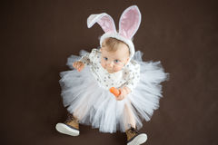 Looking up. Cute baby with carrot on brown Royalty Free Stock Images