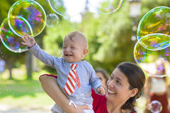 Cute Baby Catching Soap Bubbles Royalty Free Stock Photos
