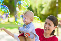 Cute Baby Catching Soap Bubbles Stock Photo