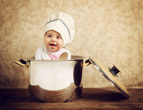 Cute baby chef in a huge cauldron. On wooden table Royalty Free Stock Photography