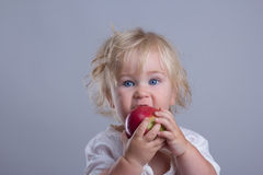 Cute baby chewing. On delicious red apple royalty free stock photography