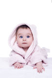 Cute baby child in pink bathrobe lying down on blanket stock image