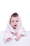 Cute baby child in pink bathrobe lying down on blanket royalty free stock photo