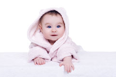 Cute baby child in pink bathrobe lying down on blanket royalty free stock images