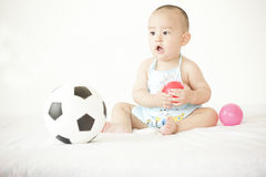 A cute baby. A Chinese baby is playing with toys in bed Royalty Free Stock Photography