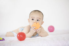 A cute baby. A Chinese baby is playing with toys in  bed and looking Stock Images