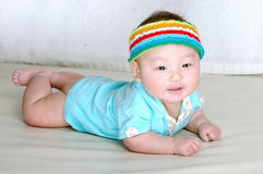 Cute baby with colorful cap. A cute baby laying on the bed with a colorful cap on head Stock Photography