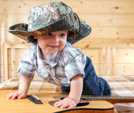 Cute baby in cowboy hat climbing the guitar. At home Royalty Free Stock Photography