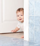 Cute baby crawling through the door Royalty Free Stock Photography