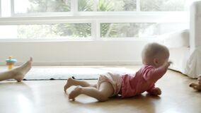 Cute baby crawling on floor from mom to dad and grasping phone
