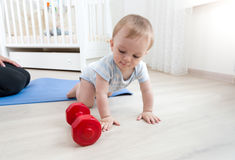 Cute baby crawling on floor and playing with dumbbells Stock Photos