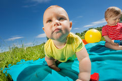 Cute baby crawling and other sitting on blanket royalty free stock photos