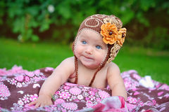 Cute baby crawling outdoors in brown knitted cap.  Stock Images