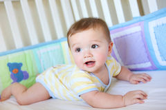 Cute Baby in Crib. A cute young baby boy in a crib smiling Stock Photos