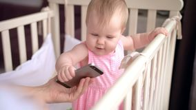 Cute baby in crib touch smartphone. Baby technology concept