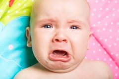 A cute baby crying on a bed stock photography