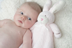 Cute baby cuddling with pink toy bunny blanket Stock Image