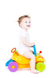 Cute baby with curly hair on a toy car Royalty Free Stock Photography