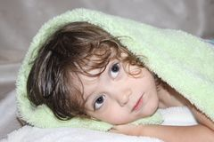 Cute baby with curly long blond hair peeking out from under the rug royalty free stock photography