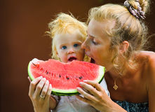 Cute baby with a delicious melon Stock Photos