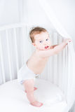 Cute baby in a diaper standing in a crib Stock Photo