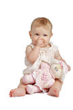 Cute baby with doll sucking thumb  in sleeveless sundress. Eight month old baby girl sits with doll on her lap and sucks her thumb. She wears a dainty sleeveless Royalty Free Stock Photo
