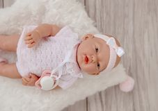 Cute Baby Doll in white pale clothes  on beige background. Baby doll in white pale clothes  on beige  background royalty free stock images