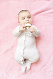 Cute baby drinking water. Cute caucasian baby drinking water from the bottle while laying down on the pink blanket. Vertical overhead shot Royalty Free Stock Image