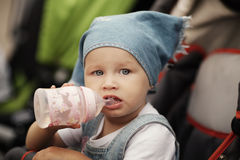 Cute baby drinks juice. Sitting in baby carriage Stock Images