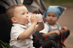 Cute baby drinks juice. Sitting in baby carriage Stock Photos