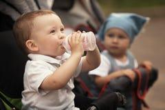 Cute baby drinks juice Stock Photos