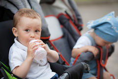 Cute baby drinks juice sitting in baby carriage. Outdoors Stock Photos