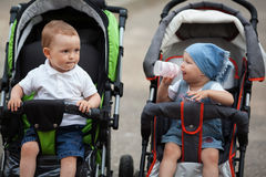 Cute baby drinks juice sitting in baby carriage. Outdoors Stock Photo