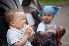 Cute baby drinks juice sitting in baby carriage Stock Photos