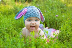 Cute baby in a Easter bunny of lamb costume i. Easter holidays! Cute baby in a Easter bunny of lamb costume in the green spring grass. Smiling baby kid posing royalty free stock photo