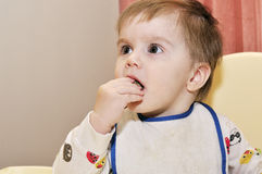 Cute baby eat with hands help. On chair Stock Photos