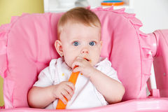 Cute baby eating carrot Royalty Free Stock Photos