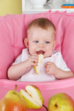 Cute baby eating fruit Stock Photography