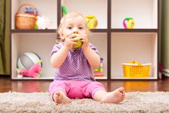 Cute baby eating a green apple Royalty Free Stock Images