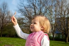 Cute baby eating lollipop at nature Royalty Free Stock Image