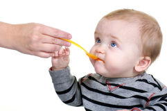 Cute Baby Eating Lunch. Cute baby being fed carrots with a yellow spoon Stock Images