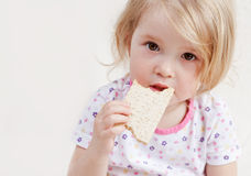 Cute baby eats. Bread on a white background royalty free stock photography