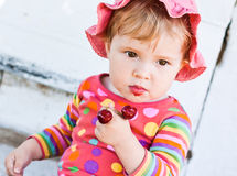 Cute baby eats cherries. Outdoors royalty free stock photo