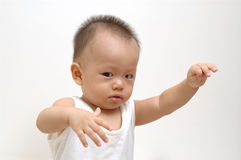 Cute baby expression. It is a cute chinese baby,raising his hand, and making a cute  expression , he is 9 months old Royalty Free Stock Photos