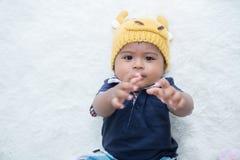 Cute baby in fancy deer hat lying on soft blanket and smiling. Cute baby in fancy deer hat lying stock photo