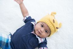 Cute baby in fancy deer hat lying on soft blanket and smiling. Cute baby in fancy deer hat lying on soft stock images