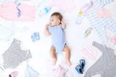 Baby with fashion clothes. Cute baby with fashion clothes lying on white bed royalty free stock image
