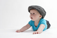 Cute baby with flat cap. Cute baby boy lying on white studio background with flat cap Stock Image